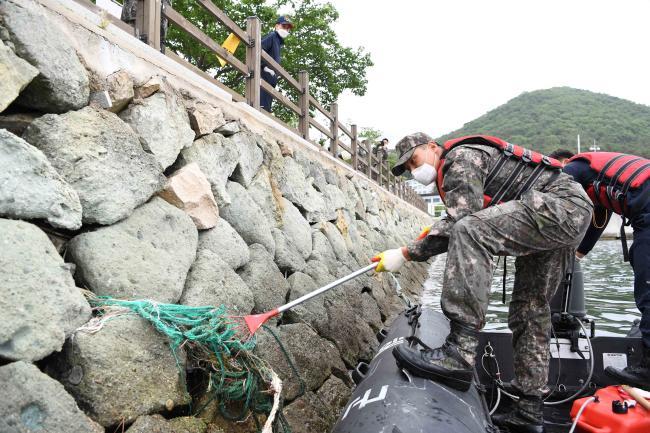 제25회 바다의 날을 앞두고 해안정화활동에 나선 해군사관학교 장병들이 21일 해사 반도 일대에서 파도에 밀려온 쓰레기를 수거하고 있다.   부대 제공