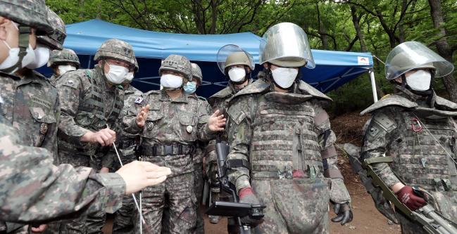 박한기(가운데) 합참의장이 25일 후방지역 방공진지 주변 지뢰제거작전 현장을 방문, 장병들을 격려하고 있다.  이경원 기자