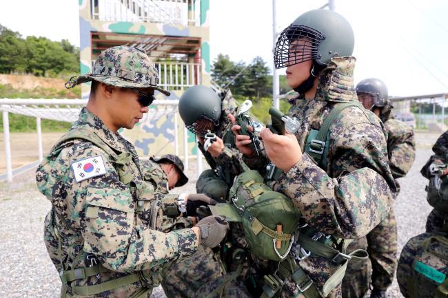 황준홍(왼쪽) 소령이 공수지상훈련을 앞둔 부대원의 복장과 장비를 점검하고 있다.