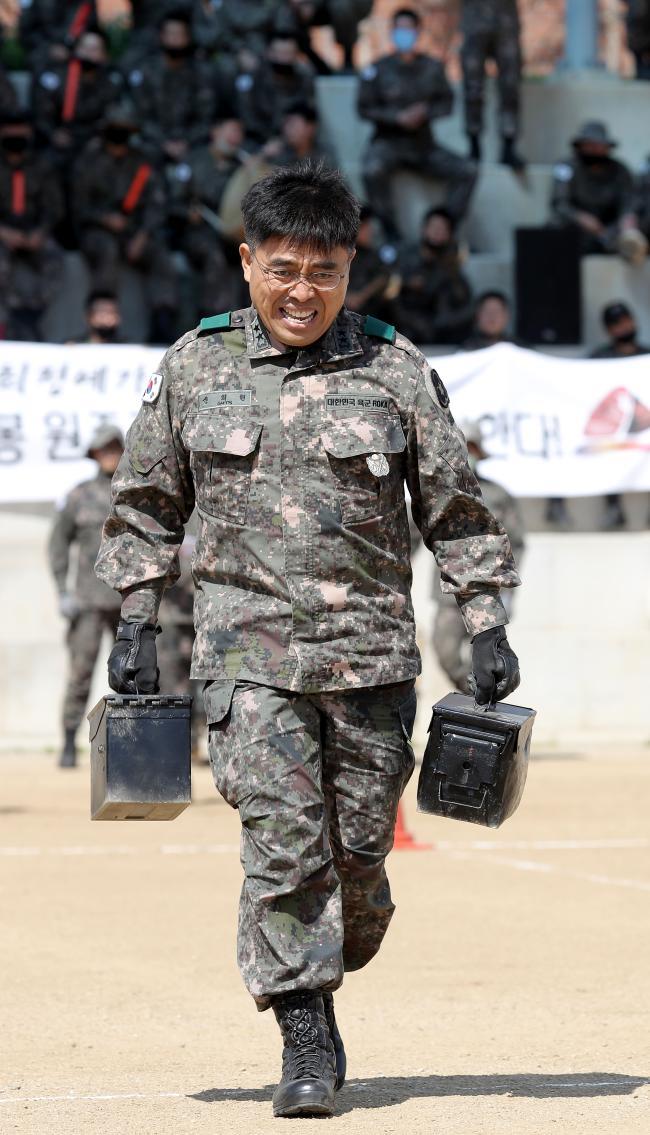 ◀  경연대회에 참가한 신희현 사단장이 15㎏ 무게 탄약통을 양손에 들고 달리기를 하고 있다.