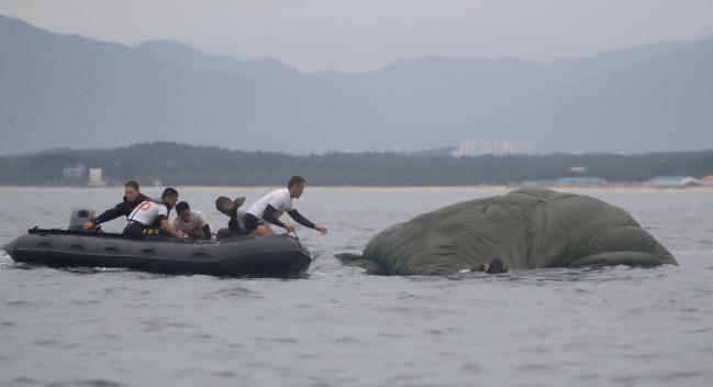 1 C-130 수송기에서 강하한 특전요원들이 고무보트에 올라탄 뒤 낙하산을 수거하고 있다. 2 C-130 수송기에서 공중 강하한 특전요원들이 고무보트를 이용해 육지로 접안하고 있다. 3 특전요원들이 C-130 수송기에서 투하한 물자 해체 교육을 받고 있다. 4 해상척후조 훈련에 참가한 특전요원들이 해안을 달리며 체력단련을 하고 있다. 사진=양동욱 기자
