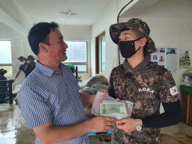 수해복구 작전 중 잃어버릴 뻔한 어머니의 유품을 전달받은 김영철(왼쪽) 씨가 39사단 기동대대 박기수 중사에게 감사인사를 전하고 있다.  부대 제공