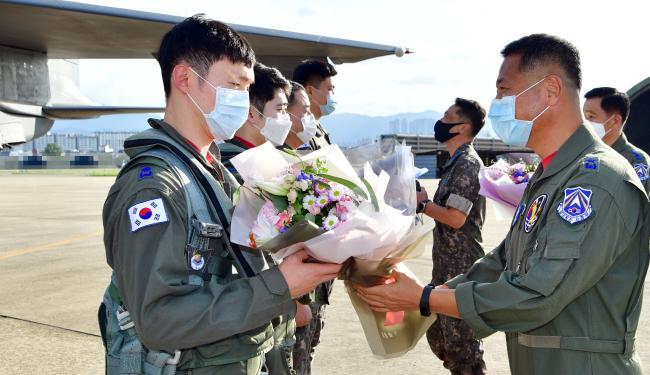 공군11전투비행단 '3만 시간 무사고 비행기록 수립' 축하 행사에서 이상학(준장·오른쪽)11전투비행단장이 조종사에게 꽃다발을 건네며 격려의 말을 하고 있다.   사진 제공=안재경 준위