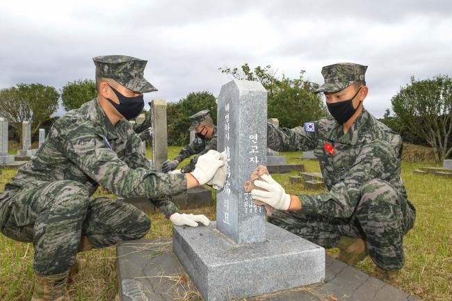 해병대 9여단 장병들이 추석을 앞두고 제주지역 내 충혼묘지에서 묘비를 닦고 있다.  부대 제공