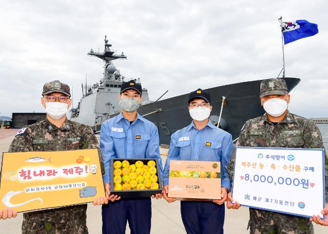 해군7기동전단 윤태두(맨 왼쪽) 보급지원대장을 비롯한 장병들이 공동구매를 통해 구입한 제주 감귤을 들고 코로나19로 어려움을 겪는 지역 주민들에게 응원의 메시지를 보내고 있다.  부대 제공