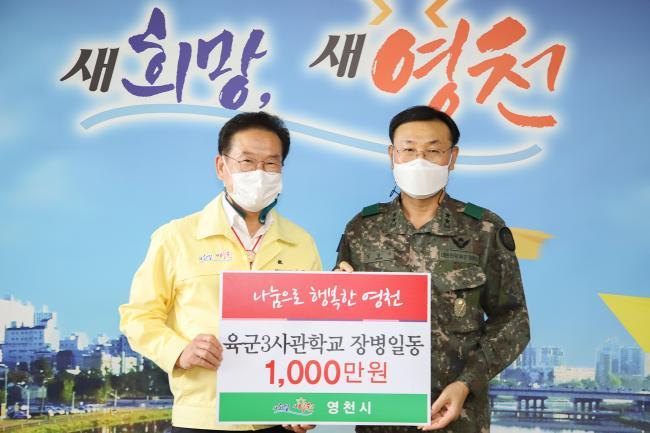 장달수(오른쪽) 육군3사관학교장이 최기문 영천시장에게 이웃돕기 성금 1000만원을 전달하고 있다.    부대 제공