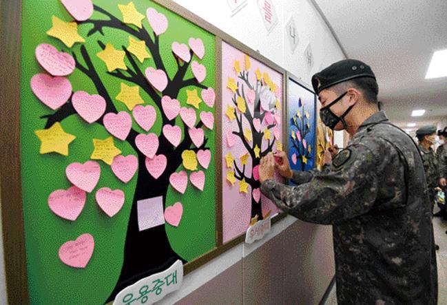 8군단 정보통신단 장병들이 부대 내 게시판에 설치된 감사나눔나무에 감사 메모를 적고 있다.사진=조용학 기자