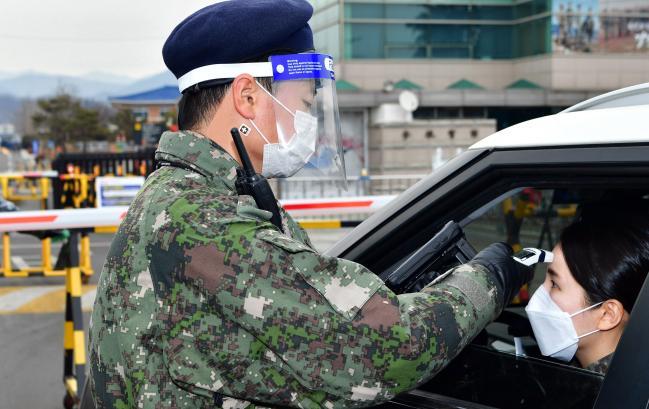 공군11전투비행단 정문에서 '페이스 실드'와 '패스밴드' 등 코로나19 보호구를 착용한 병사가 출입통제 임무를 수행하고 있다.  부대 제공