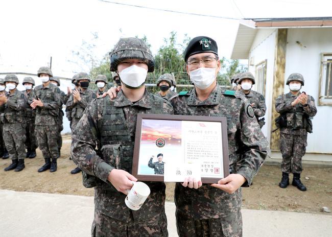 강창구(오른쪽) 8군단장이 완벽한 해안경계작전태세 확립에 기여한 22사단 이경범 일병에게 자랑스러운 충용인상을 수여한 뒤 기념사진을 찍고 있다.  부대 제공