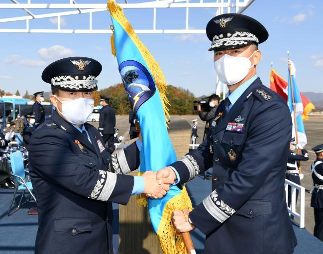 이성용(왼쪽) 공군참모총장이 3일 충주기지에서 거행된 '39정찰비행단 창설식'에서 초대 정찰비행단장인 박기완 준장(진)에게 지휘권의 상징인 부대기를 수여하고 있다.  공군 제공