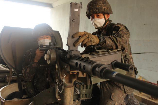 여단 전투지휘검열에 참가하고자 최근 전역을 일주일 연기한 육군2기갑여단 번개대대 안대희 병장이 후임병에게 K6 기관총 운용 노하우를 전수하고 있다.  부대 제공