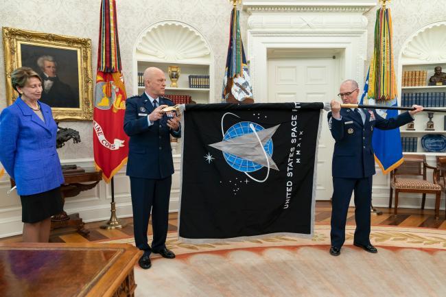 미 우주군 사령부는 2019년 12월 공군과 분리된 독자적인 군으로 창설됐다. 사진에서 초대 우주군 작전사령관인 존 윌리엄 레이몬드(가운데) 대장이 2020년 5월 백악관에서 부대기를 펼쳐 보이고 있다. 부대기 가운데 델타 마크는 이 부대의 전신인 미공군우주사령부(AFSC) 방패에 있던 것으로 역사적 기원을 보여주고 있다. 상단의 빛나는 별은 국가안보를 지켜주는 북극성을 상징하고 양 옆 3개의 별은 우주군의 조직, 훈련, 무장을 강조한다.  필자 제공