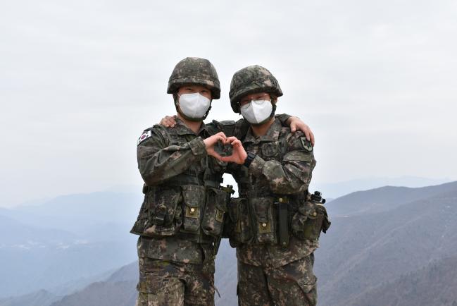 ▶ 육군12사단 향로봉대대에서 복무 중인 문승환(왼쪽) 상병, 문대환 일병이 서로를 격려하며 손 하트를 그려 보이고 있다.   사진 제공=김은택 중위