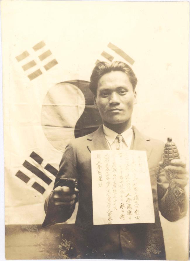 왼손에 폭탄, 오른손에 권총을 들고 태극기 앞에서 절명사를 가슴에 붙이고 사진을 찍은 윤봉길 의사.