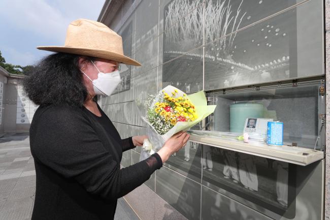 지난 21일 국립이천호국원에 있는 6·25 참전용사 고(故) 박근하 육군하사의 묘역에 딸 박순덕 씨가 꽃을 바치고 있다.