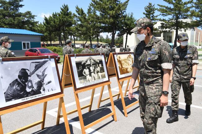 공군18전투비행단 장병들이 호국 안보 주간에 진행된 6·25 상기 부대 역사 사진전에 전시된 사진들을 관람하고 있다.  사진 제공=박의찬 하사