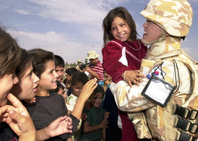 2004년 10월 자이툰부대원이 이라크 아르빌 시내에서 어린이들과 반갑게 인사를 나누고 있다.  국방일보 DB