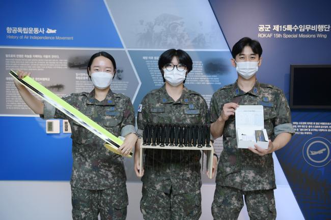 공군15특수임무비행단 김성은(가운데) 하사가 보급업무 개선 아이디어 경연대회에 공모한 아이디어 물품을 들고 동료들과 사진을 찍고 있다.   사진 제공=김샛별 중사