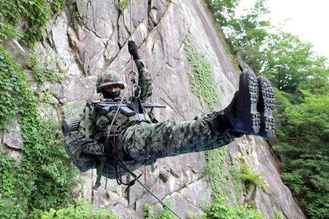 화산유격훈련장에서 진행된 산악극복훈련에서 육군특수전사령부(특전사) 예하 독수리부대 황소대대 유근혁 상사가 30㎏의 완전군장을 메고 암벽에서 하강훈련을 하고 있다. 산악극복훈련은 유사시 적지로 침투해 험준한 산과 계곡을 넘나들며 신속하게 주어진 임무를 완수하기 위한 것으로 강하훈련, 해상침투훈련 등과 함께 특전사를 대표하는 훈련 중 하나다. 특전사 예하 전 부대는 연례적으로 산악극복훈련을 반드시 시행한다.  2021년 6월 23일 경북 군위=조종원 기자