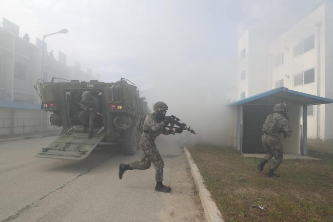 워리어 플랫폼을 장착한 전투원들이 K808 차륜형 장갑차에서 내린 뒤 적을 소탕하기 위해 건물 안으로 진입하고 있다.
